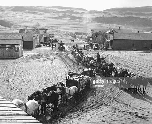 A wagon train drives down the main street in a small farming comuunity Undated photograph circa 1880 BPA2#5148