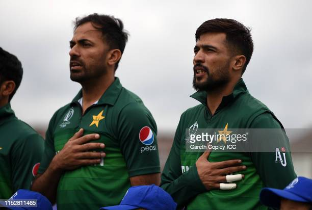 Wahab Riaz and Mohammad Amir of Pakistan line up for the national anthems during the Group Stage match of the ICC Cricket World Cup 2019 between West...