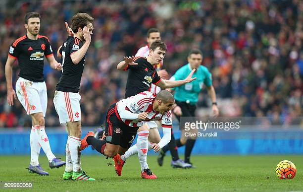 Wahbi Khazri of Sunderland is challenged by Donald Love of Manchester United during the Barclays Premier League match between Sunderland and...