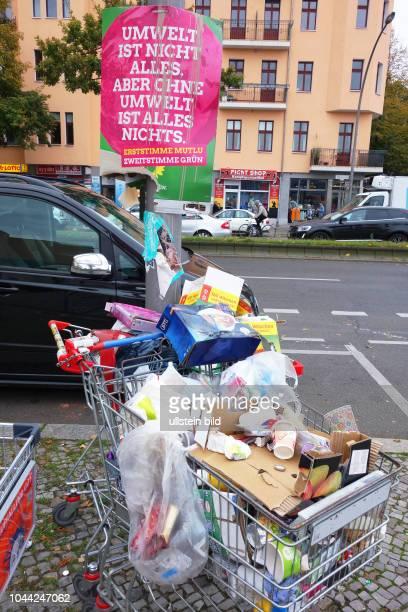Wahlplakate zur Bundestagswahl 2017 in Berlin am Wahlplakat der Partei BÜNDNIS 90/DIE GRÜNEN mit dem Slogan UMWELT Herrenlose Einkaufswagen mit Müll...