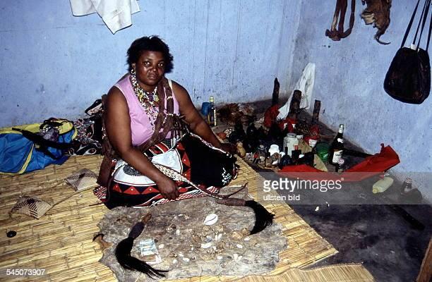 Wahrsagerin in Maputo auf dem Fell vor ihr Utensilien zum Wahrsagen 1999