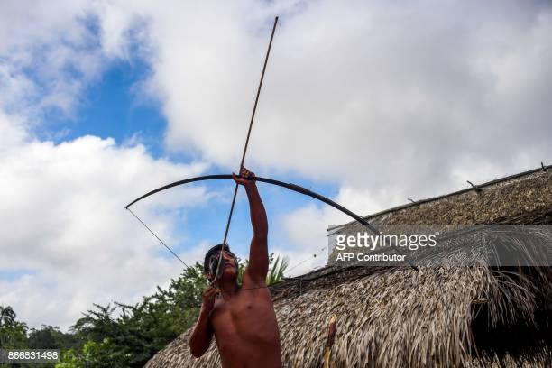 Waiapi man aims bow and arrow at the Waiapi indigenous reserve in the Manilha village, in Amapa state, Brazil, on October 13, 2017. The Waiapi are...