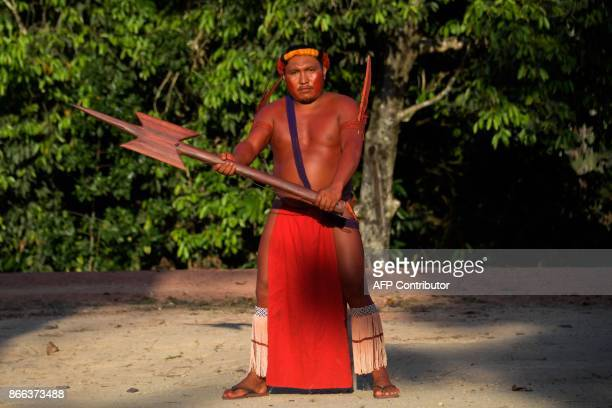 A Waiapi man poses for a picture with his wooden Borduna during the Anaconda's party during which they make flutes to play and dance and at the end...