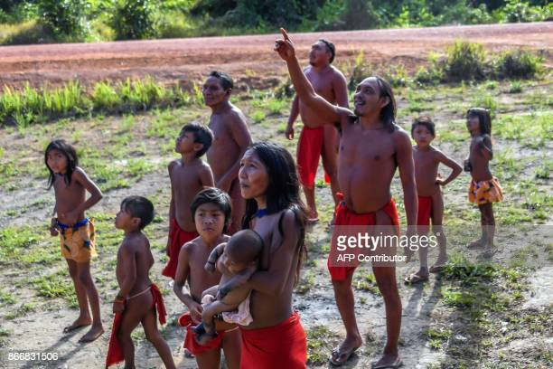 Waiapi people look at an airplane flying over the Waiapi indigenous reserve in Amapa state in Brazil on October 15, 2017. The Waiapi are one of the...