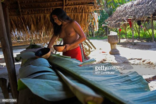 A Waiapi woman prepares Caxiri a craft beer made with Manioc imbibed daily by men women and children when is not yet sour yet at the indigenous...