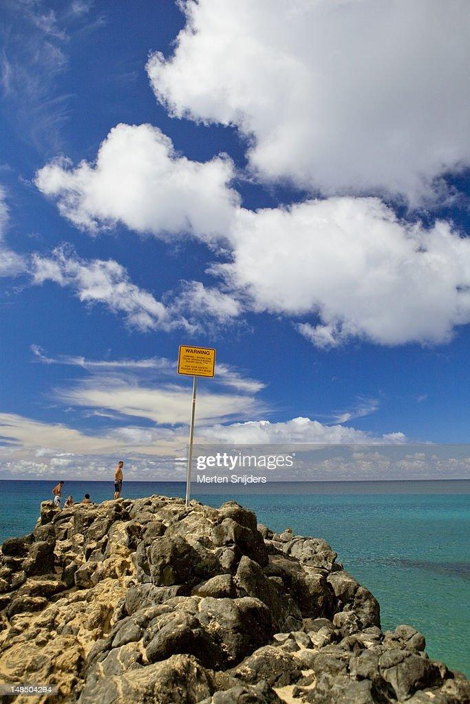 Waimea Bay boulder with warning sign. : Stockfoto