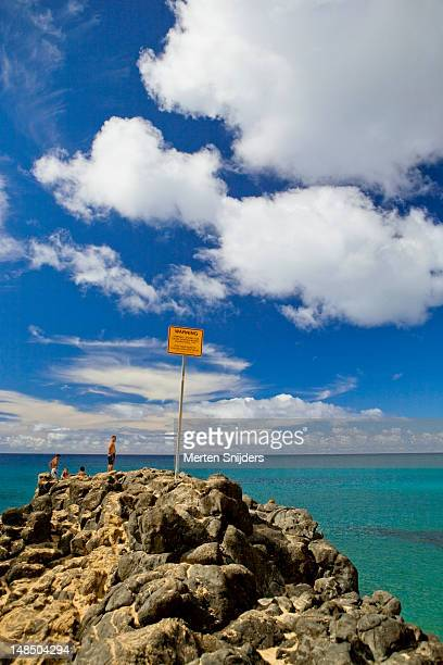 waimea bay boulder with warning sign. - merten snijders stock pictures, royalty-free photos & images