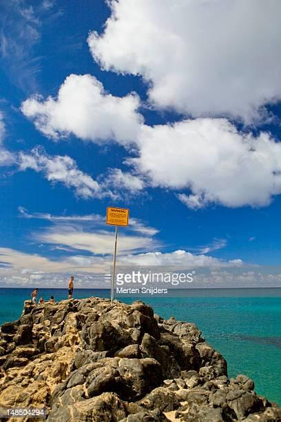 waimea bay boulder with warning sign. - merten snijders stockfoto's en -beelden