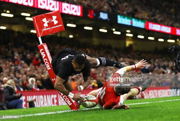 Waisake Naholo of New Zealand touches down for the first try while under pressure from Steff Evans of Wales during the International match between...