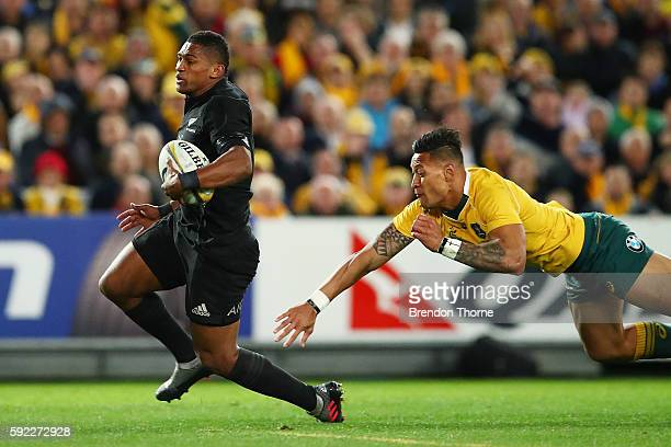 Waisake Naholo of the All Blacks avoids the tackle attempt from Israel Folau of the Wallabies during the Bledisloe Cup Rugby Championship match...