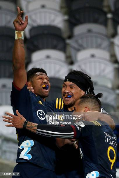 Waisake Naholo of the Highlanders celebrates his try with team mates Aaron Smith and Aki Seiuli during the round 16 Super Rugby match between the...