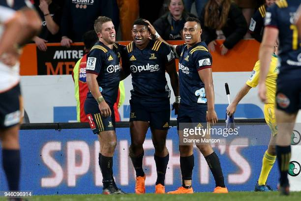 Waisake Naholo of the Highlanders celebrates his try with teammates Teihorangi Walden and Tevita Li of the Highlanders during the round nine Super...