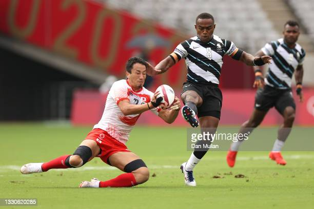 Waisea Nacuqu of Team Fiji and Naoki Motomura of Team Japan compete for the ball on day three of the Tokyo 2020 Olympic Games at Tokyo Stadium on...