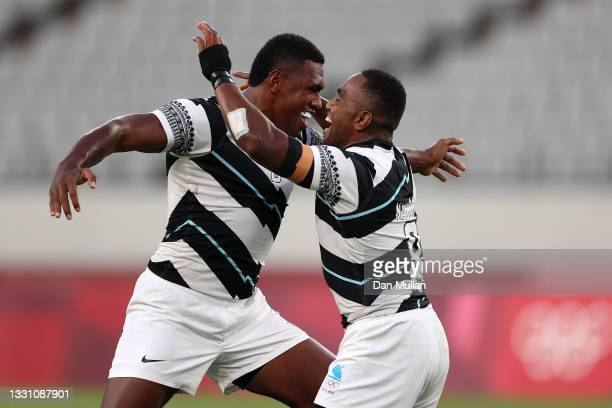 Waisea Nacuqu of Team Fiji celebrates victory with Kalione Nasoko of Team Fiji during the Rugby Sevens Men's Gold Medal match between New Zealand and...
