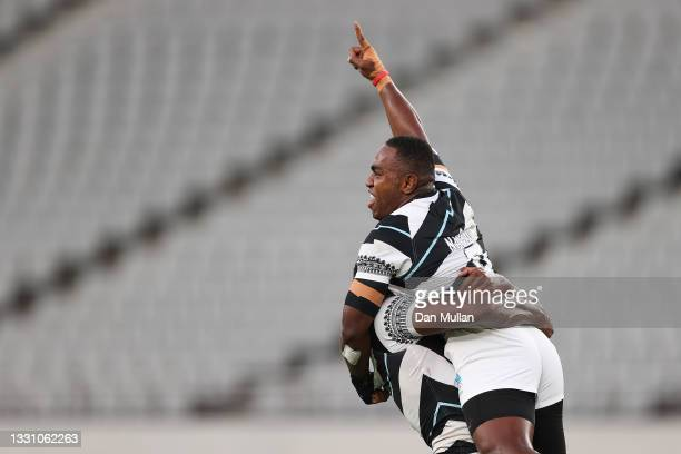 Waisea Nacuqu of Team Fiji is lifted by Kalione Nasoko during the Rugby Sevens Men's Gold Medal match between New Zealand and Fiji on day five of the...