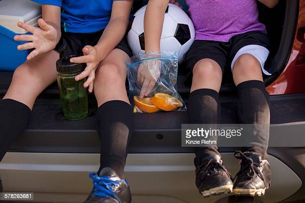 Waist down of boy and younger sister sitting in car boot eating oranges on football practice break