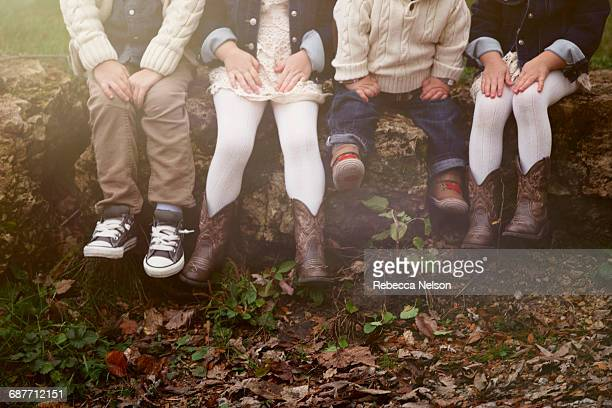 waist down of four children seated on rocks in par - bambini in mutande foto e immagini stock