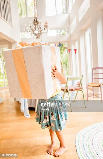 Waist down of girl at birthday party carrying large birthday present