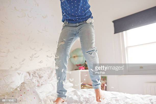 Waist down of girl jumping and feather pillow fighting on bed