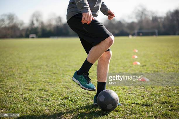 Waist down of young man practicing soccer on playing field