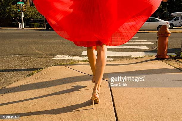 Waist down shot of young woman strolling along sidewalk wearing flowing red skirt