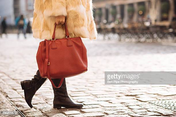 Waist down view of stylish young woman wearing fur coat in Covent Garden, London, UK