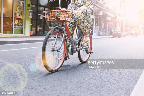 waist down view of woman cycling along street, shanghai french concession, shanghai, china - parte inferior - fotografias e filmes do acervo