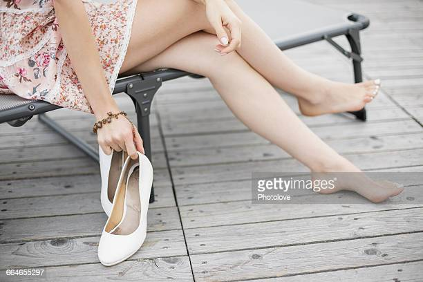 Waist down view of young woman removing high heels on park bench