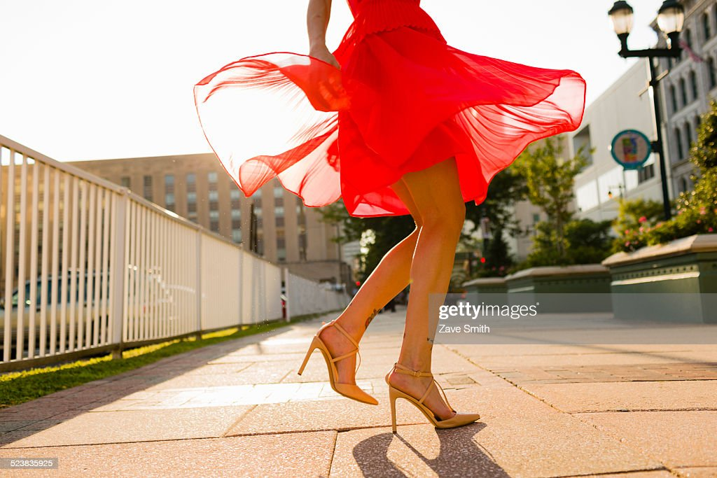 Waist down view of young woman twirling whilst wearing red dress : Stock Photo