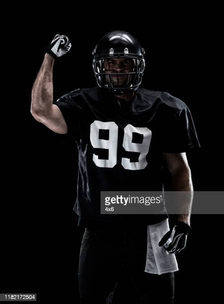 waist up / one man only / one person / front view of adult handsome people caucasian young men / male american football player / athlete standing in front of black background wearing helmet / sports helmet and celebration / cheering / showing fist - football photoshoot stock pictures, royalty-free photos & images
