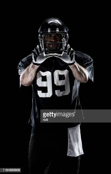 waist up / one man only / one person / front view of adult handsome people caucasian young men / male american football player / athlete standing in front of black background wearing helmet / sports helmet and celebration and using sports ball - football photoshoot stock pictures, royalty-free photos & images