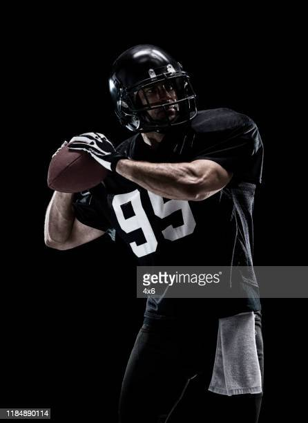 waist up / one man only / one person / front view of adult handsome people caucasian young men / male american football player / athlete standing in front of black background wearing helmet / sports helmet who is a sex symbol / of muscular build - football photoshoot stock pictures, royalty-free photos & images