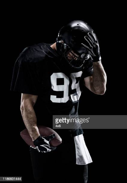 waist up / one man only / one person / front view of adult handsome people caucasian young men / male american football player / athlete standing in front of black background wearing helmet / sports helmet who is lost and using sports ball - football photoshoot stock pictures, royalty-free photos & images