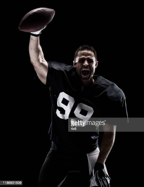 waist up / one man only / one person / front view of adult handsome people caucasian young men / male american football player / athlete standing in front of black background who is a sex symbol / of muscular build / successful and winning - football photoshoot stock pictures, royalty-free photos & images