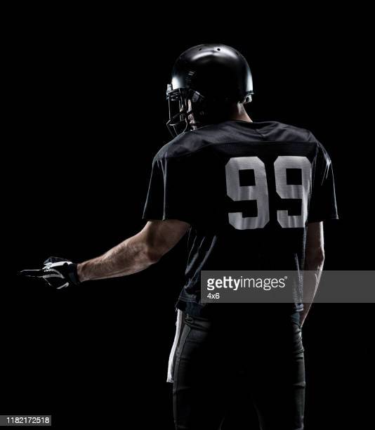 waist up / one man only / one person / rear view / back of adult handsome people caucasian young men / male american football player / athlete / presenter standing in front of black background wearing helmet / sports helmet who is showing / pointing - football photoshoot stock pictures, royalty-free photos & images