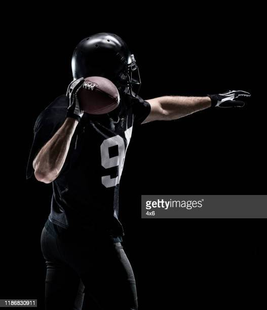 waist up / one man only / one person / rear view / back of adult handsome people caucasian young men / male american football player / athlete standing in front of black background wearing helmet / sports helmet who is throwing / catching - football photoshoot stock pictures, royalty-free photos & images