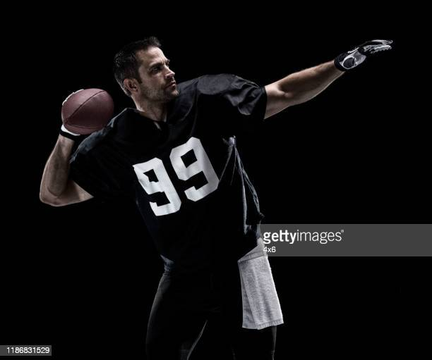 waist up / one man only / one person / side view / profile view of adult handsome people caucasian young men / male american football player / athlete standing in front of black background who is a sex symbol / of muscular build and using sports ball - football photoshoot stock pictures, royalty-free photos & images
