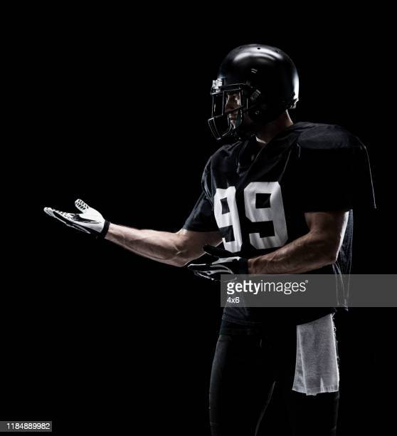 waist up / one man only / one person / sideways glance / looking away of adult handsome people caucasian young men / male american football player / athlete / presenter standing in front of black background wearing helmet / sports helmet / presenting - football photoshoot stock pictures, royalty-free photos & images