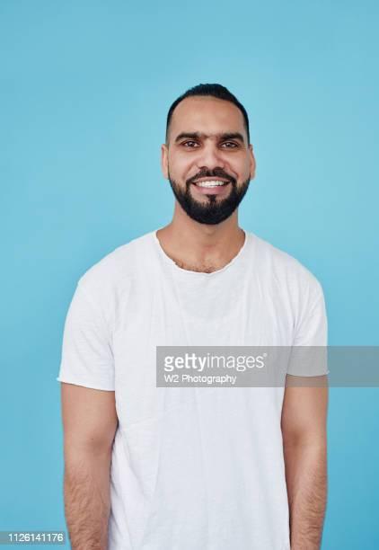 a waist up portrait of a smiling indian man on a blue background. - männlichkeit stock-fotos und bilder