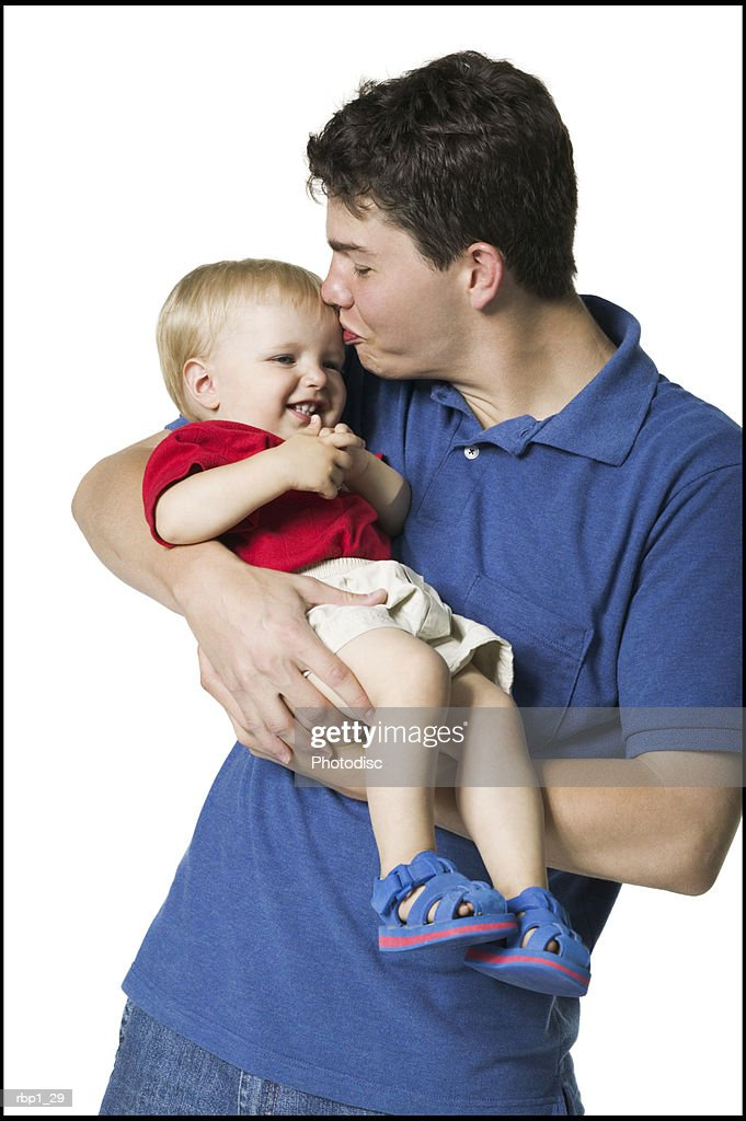 waist up portrait of a young adult male as he holds up and kisses his baby : Stockfoto