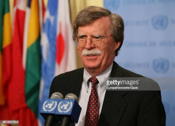 Waist up portrait of politician John Bolton speaking at the United Nations headquarters in New York City New York with colorful flags in background...