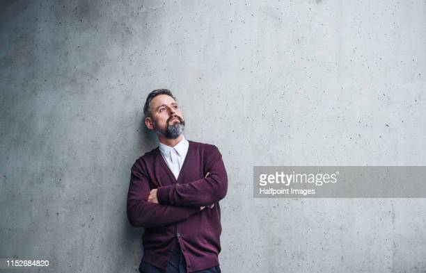 a waist up portrait of serious mature businessman standing against a concrete wall. copy space. - mirar hacia arriba fotografías e imágenes de stock