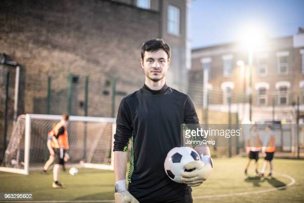 waist up portrait of young man looking at camera and holding football in goalkeeper's kit - amateur stock pictures, royalty-free photos & images