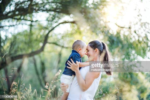 A waist up portrait of young mother holding a toddler son outdoors in nature in summer, having fun.