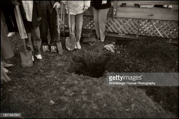 Waist-down view of a group of people, several of whom hold shovels, as they stand beside a newly dug hole during a groundbreaking ceremony for a...