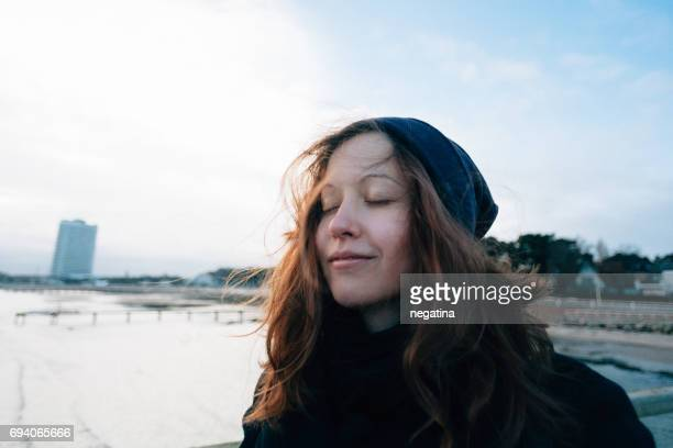waist-up of young woman with closed eyes and smiling on the Travemuende beach in Germany