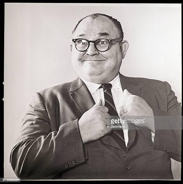 Waist-up portrait of a smiling man holding his jacket lapels. Undated photograph.