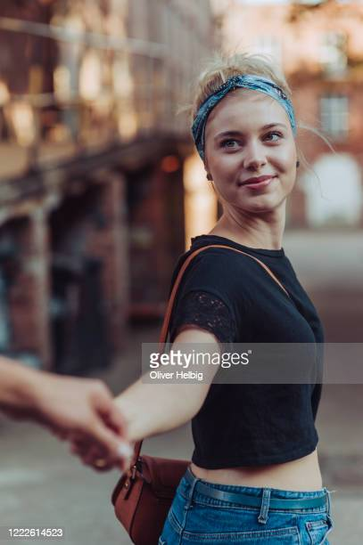 waist-up portrait of happy young blond woman is holding hand with his boyfriend going behind her. she is looking behind with bright smile. - 人体部位 ストックフォトと画像