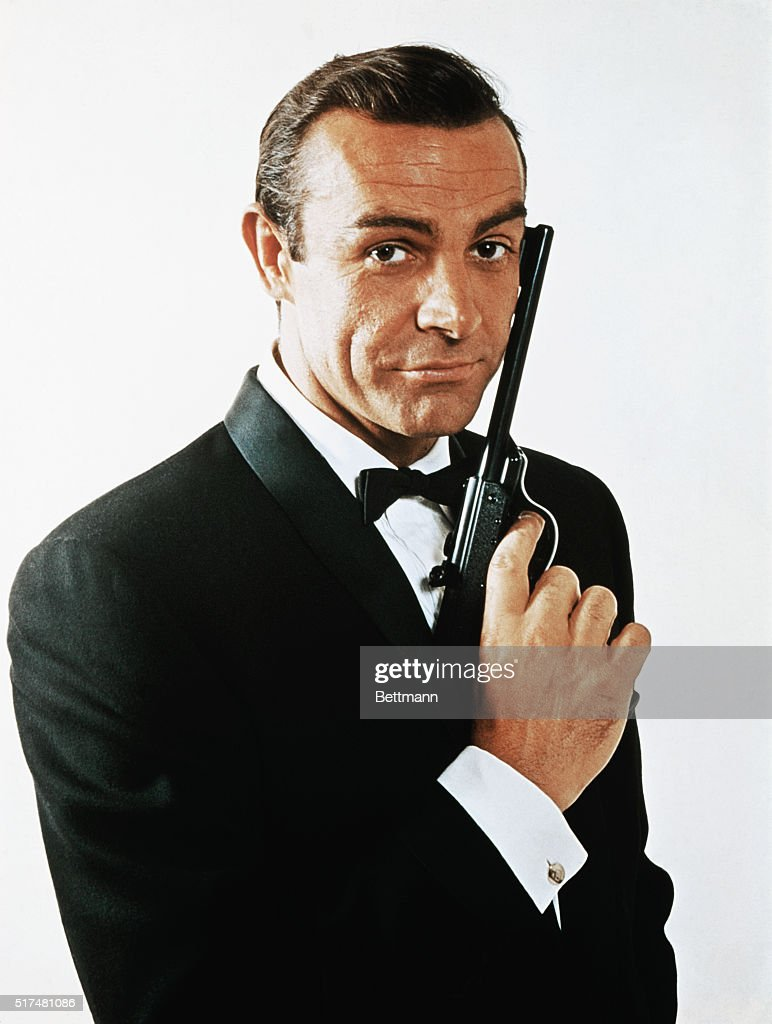 Waist-up portrait of Sean Connery, as James Bond, caressing the barrel of a gun against the side of his face. Connery is wearing a tuxedo and bow tie and smiling slightly.