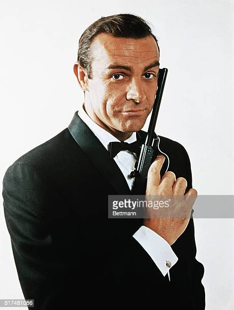 Waist-up portrait of Sean Connery, as James Bond, caressing the barrel of a gun against the side of his face. Connery is wearing a tuxedo and bow tie...